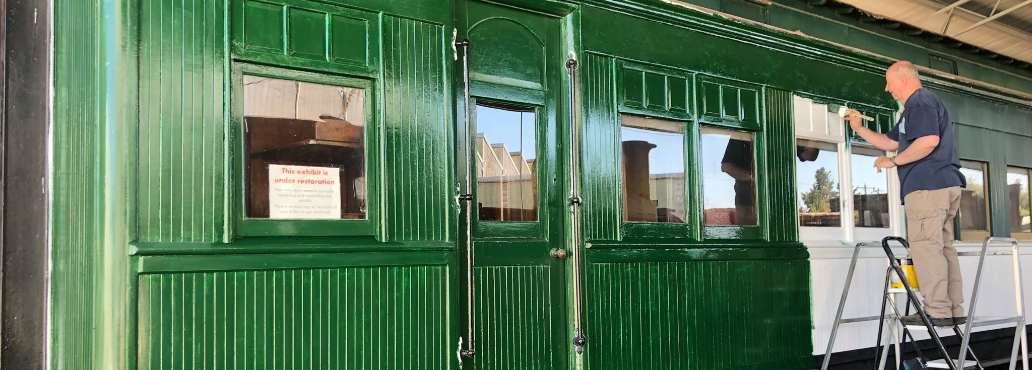 Man repainting side of green carriage