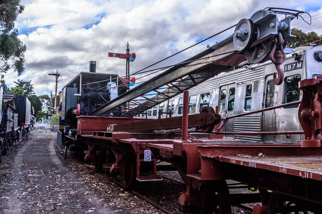 Black steam crane with red wagons in front