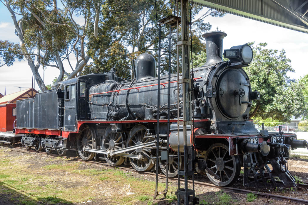 Black steam locomotive with horizontal red stripe numbered D3 635
