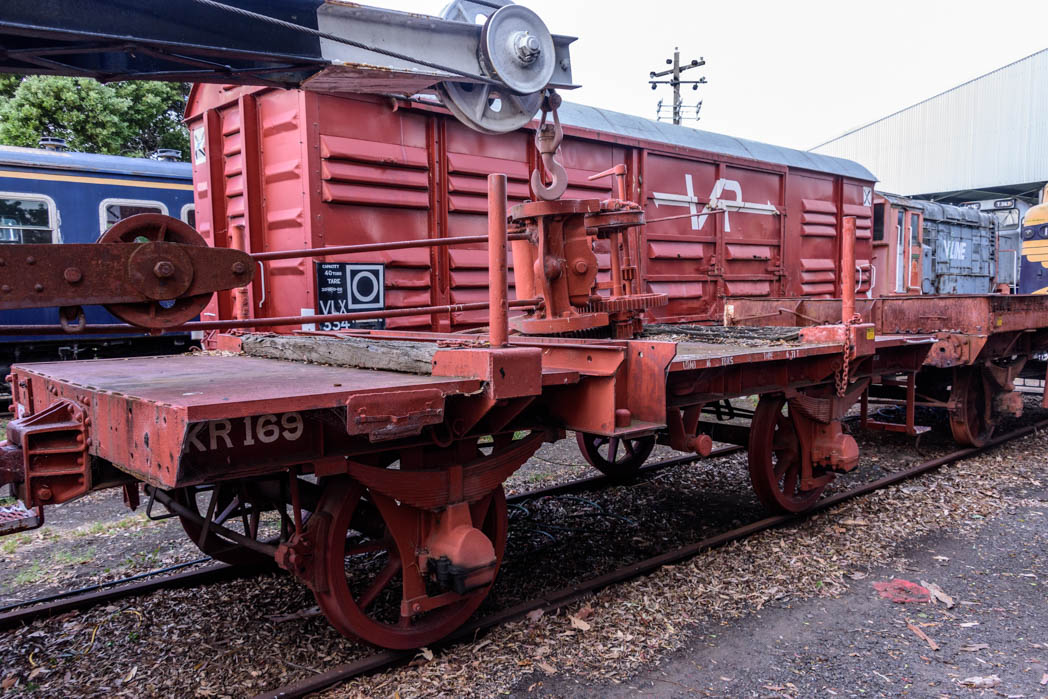 Red wagon with four wheels and a crane mechanism sitting on top