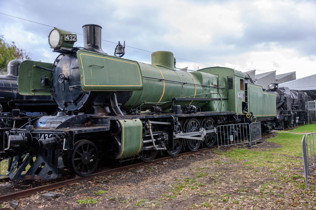 Green steam locomotive with vertical gold stripes numbered N 432